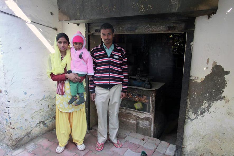 Janvi with her parents, outside their small shop.